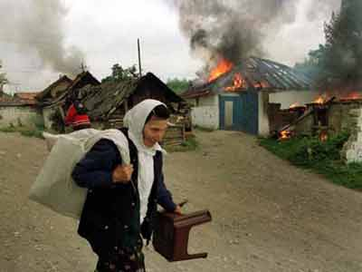 An Albanian woman looting - Serb houses burning in the background